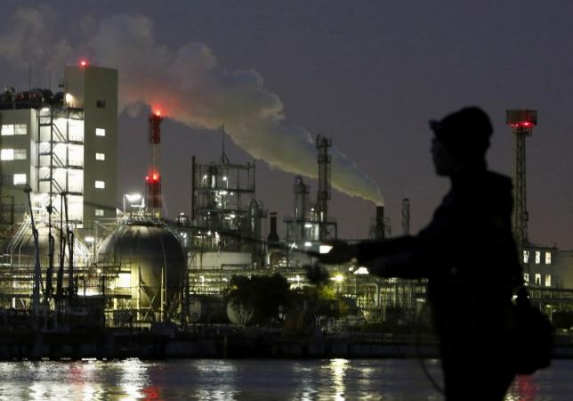 Smoke is emitted from a chimney as a man fishes at the Keihin industrial zone in Kawasaki