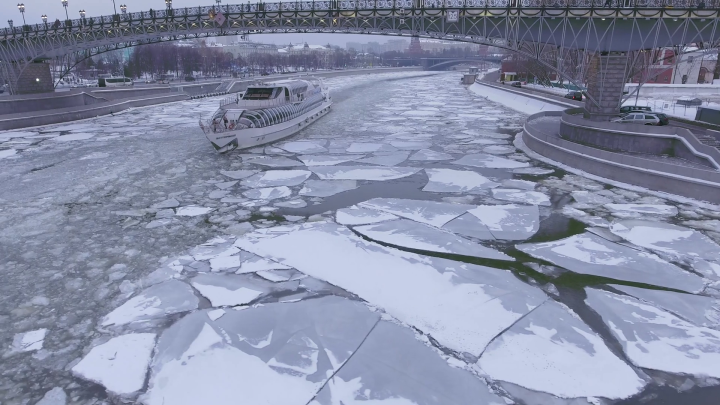 frozen-moscow-river-cruise-ship-icebreaker-brake-the-ice-day-near-kremlinunique-aerial-drone-4k-footage-in-the-center-of-capital-of-russia-snow-winter-under-the-bridge_hglrcnsfe_thumbnai