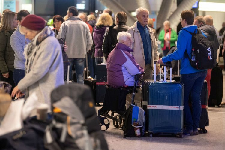 Passengers wait Thursday morning at the Stuttgart airport, after their flight was cancelled, for a bus to take them to the Baden Airport for an alternative flight. Photo: DPA